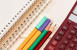 Colored pencils, desktop calculator and notebooks on white wooden table.  School and office supplies. Top view stock photos