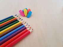 Colored Pencils And Erasers Laying On A Light Wooden Background, School Supplies royalty free stock photos