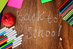 Colored pencils, felt-tip pens and markers, notebooks, stickers  a red apple on the wooden background with the back to Stock Photos
