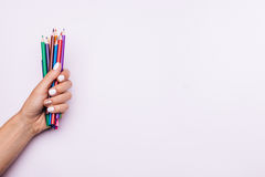 Colored pencils in a female hand with white manicure on a light stock photography