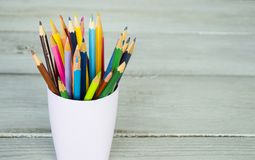 Colored pencils in a glass on a wooden background. Template for creative projects Royalty Free Stock Photo