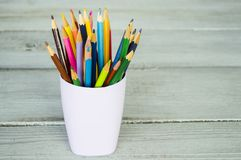 Colored pencils in a glass on a wooden background. Template for creative projects Stock Photo