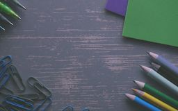 Colored Pencils on a Gray Desk With Paper Clips and Folders Royalty Free Stock Photography