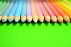 Colored pencils on green background Stock Images