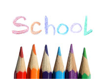 Colored pencils and the handwritten word School on white background. Colored pencils and the handwritten word School on white stock images