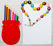 Colored pencils and heart of beads Stock Images
