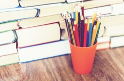 Colored pencils in holder with Stack of book education concept background stock images