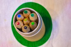 Colored pencils inserted in a cardboard cylinder on a colored pl. Ane, horizontal image royalty free stock photos