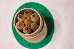 Colored pencils inserted in a cardboard cylinder on a colored pl. Ane, horizontal image stock photo