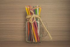 Colored pencils inside glass cup royalty free stock images