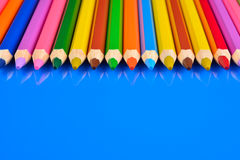 Colored pencils isolated on blue background with reflection Royalty Free Stock Photos
