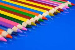 Colored pencils isolated on blue background with reflection Royalty Free Stock Images