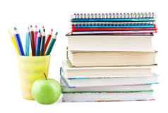 Colored pencils in jar with textbooks and apple. On white background stock photo