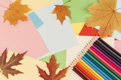 Colorful pencils lying on colorful cardboard sheets royalty free stock images
