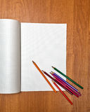 Colored pencils lie on notebook. School. Stock Image