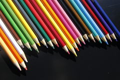 Colored pencils. Lined up on dark background stock images