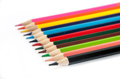 Colored pencils lined up on a white background Royalty Free Stock Images