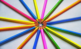 Colored pencils lined on a white sheet of paper. Multicolored pencils are lined on a white sheet of paper with slips in the center Royalty Free Stock Photo