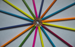 Colored pencils lined on a white sheet of paper. Multicolored pencils are lined on a white sheet of paper with slips in the center Royalty Free Stock Photography