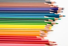 Colored pencils lying in irregular row Royalty Free Stock Images