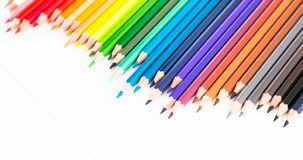 Colored pencils lying in irregular row. On white background stock photography