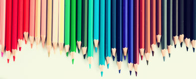 Colored pencils lying in irregular row Stock Images