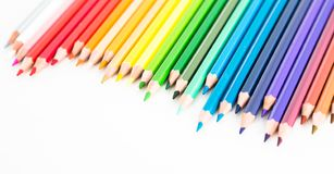 Colored pencils lying in irregular row Royalty Free Stock Photos