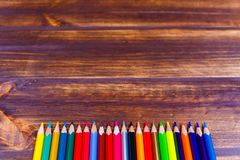 Colored pencils lying in a row on wooden surface stock photo