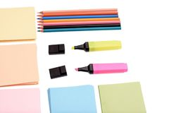 Colored pencils and markers with paper for writing isolated on white background stock images
