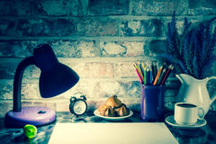 Colored pencils in a mug, vase of lavender flowers, clock, white paper Royalty Free Stock Image