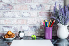 Colored pencils in a mug, vase of lavender flowers, clock, white paper Stock Images