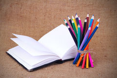 Colored pencils and notebook Stock Photos