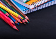 Colored pencils and a notebook on  dark background Royalty Free Stock Photography