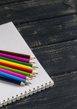 Colored pencils and notebook Royalty Free Stock Image