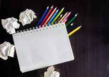 Colored pencils and notebook on wood texture. Background for painting, drawing and sketching Royalty Free Stock Photo