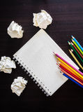 Colored pencils and notebook on wood texture. Background for painting, drawing and sketching Royalty Free Stock Photos