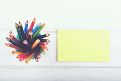 Colored pencils. And notebook on a wooden table Royalty Free Stock Photo