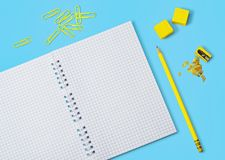 Colored pencils, notepad and other school accessories. Yellow pencil, grid notepad, yellow erasers, yellow pencil sharpener and yellow paper clips on blue Stock Photo