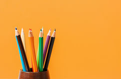 Colored pencils on orange background. Creative Art Background with colored pencils on orange background Stock Image