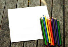 Colored pencils with painted sun. On wooden desk Royalty Free Stock Photo