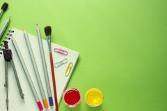 Colored pencils, paints, compasses, paper clips and brushes on a notebook, green background with copy space stock photo
