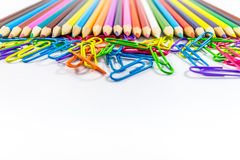 Colored pencils and paper clips. On a white background Stock Image