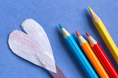Colored pencils and paper heard on blue paper background Royalty Free Stock Images