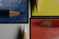Colored pencils on colored papers arranged as a crossroads. Colored pencils on colored corners arranged as a crossroads with full colors Royalty Free Stock Photography