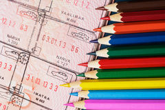 Colored pencils and a passport. spoiled documents. Risk of spoiling documents before traveling Stock Photos