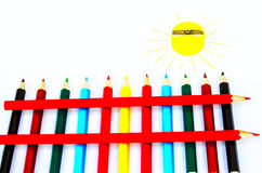 Colored pencils and pencil sharpener in the form of a yellow sun Royalty Free Stock Photography