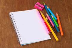Colored pencils, pencil sharpener and notebook Royalty Free Stock Photography