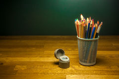 Colored pencils and pencil sharpener on the table Stock Photo