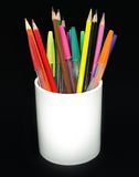 Colored pencils and pens in a jar. Against a black background royalty free stock photography
