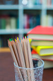 Colored pencils with pile of books in background Royalty Free Stock Image